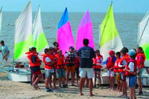 groupe d'enfants sur la plage devant des bateaux